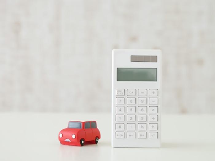 赤いミニカーと白い電卓